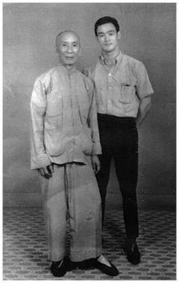 Bruce Lee stands with his Wing Chun instructor Ip Man. Source: Blackbelt Archive.