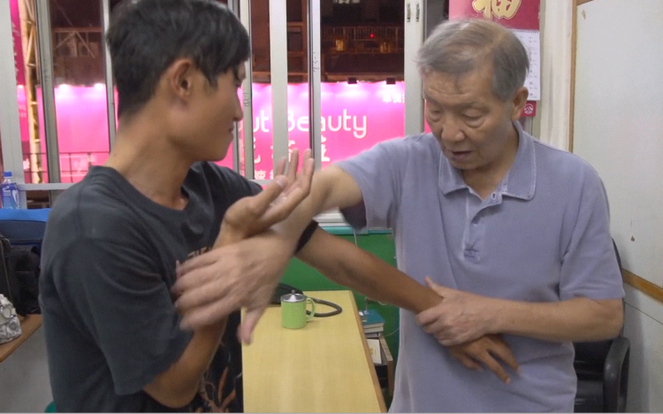 Ip Ching, the younger son of Ip Man, discussing Chi Sao techniques with a teenage student at the VTAA headquarters in Hong Kong.