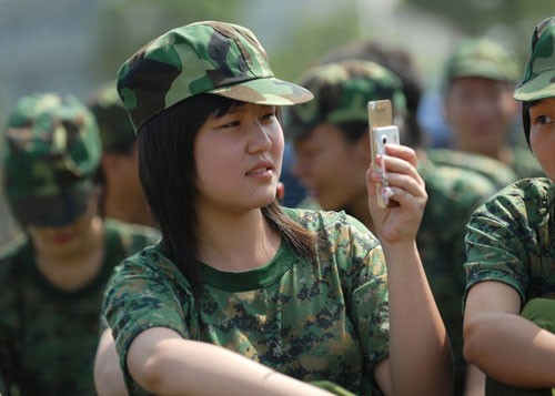A Chinese teen uses her cell phone during militia training.  This photo engendered some controversy on the internet and seemed to embody much of what was wrong with the current generation to older Chinese citizens. (Source: China Smack).
