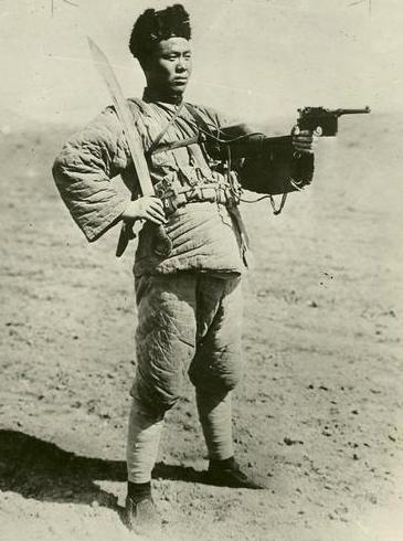 Member of a northern Warlord Army displays his Mauser handgun and Dadao.  This picture probably dates to the 1920s.