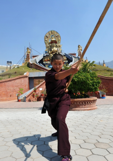 "A ""Kung Fu"" nun demonstrates a pole form at a Tibetan Temple in Nepal. Nuns from this order recently traveled to CERN Switzerland where they displayed their skills and discussed ""energy"" with a set of confused particle physicists."
