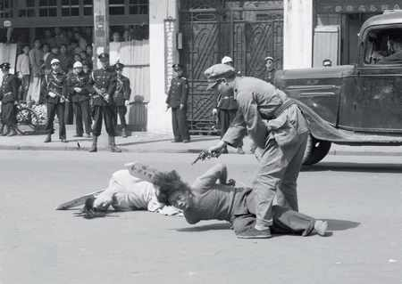 As the Communist advance accelerated in 1949 the Nationalists resorted to more desperate measure in an attempt to hold on to power in at least part of the country.  Here a Chinese officer executes two suspected communist agents in the street as a crowd of police officers and civilians looks on.