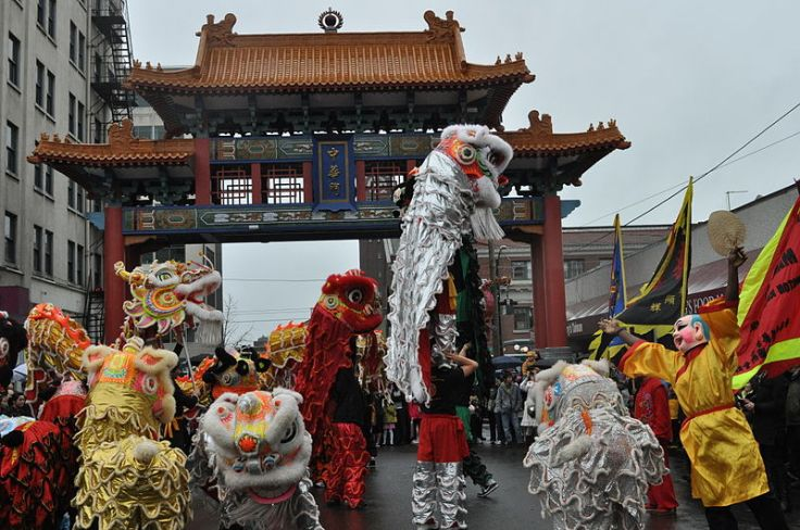 Lion dancers at Historic Chinatown Gate, Chinese New Year, Hing Hay Park, Seattle, Washington.  Source: Wikimedia.