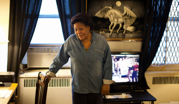 Alejandrina Cruz at her apartment in the Bronx, Kung Fu film playing in the background.  Source: New York Times.