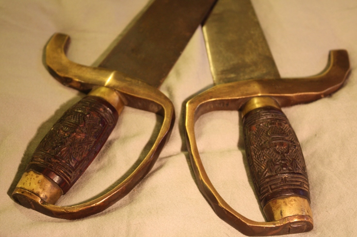 Ornately carved rosewood handles on a pair of 19th century hudiedao. This pair features both bat and floral motifs. The heavy brass handguards are shaped like bamboo and could easily be used as knuckle-dusters. Source: Authors personal collection.