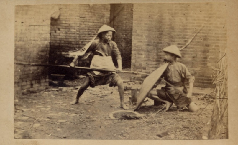 Youth engaged in militia training outside of Guangzhou in the 1850s. Note the long thin blade being held behind the rattan shield by the kneeling individual. source http://www.swordsantiqueweapons.com.
