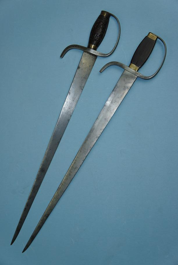 A set of mid. 19th century hudiedao. These swords are 63 cm long have strong blades with a thick triangular spine (14 mm at the forte). They were capable of cutting but clearly optimized for stabbing. The edge itself has a convex grind on one side, and a flat grind where it sits against the other sword when sheathed. The blades also feature steel D-guards and rosewood handles decorated with carved phoenixes. This images was provided courtesy of http://www.swordsantiqueweapons.com, a reliable source for authentic antique Chinese arms.