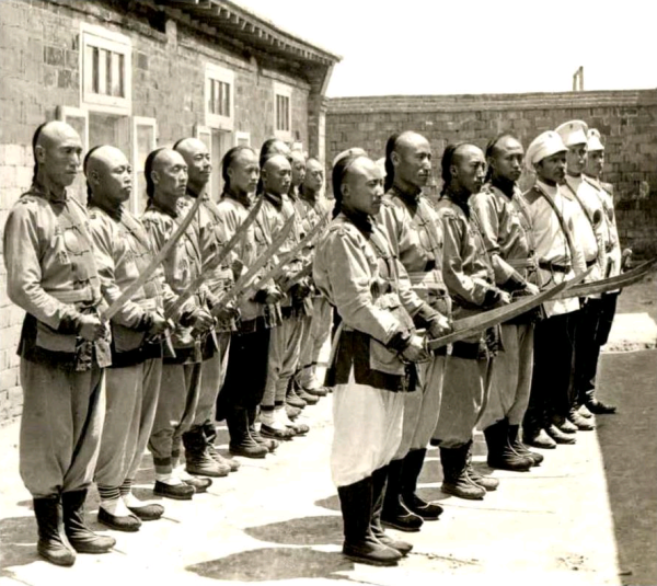 Chinese police officers employed by the Russians, probably in Port Arthur.  Circa 1900.  Note the modern, western style swords, that have been issued to this unit.  The transition to western arms was almost complete by 1890.  Source: Image taken from a vintage stereoscope slide.