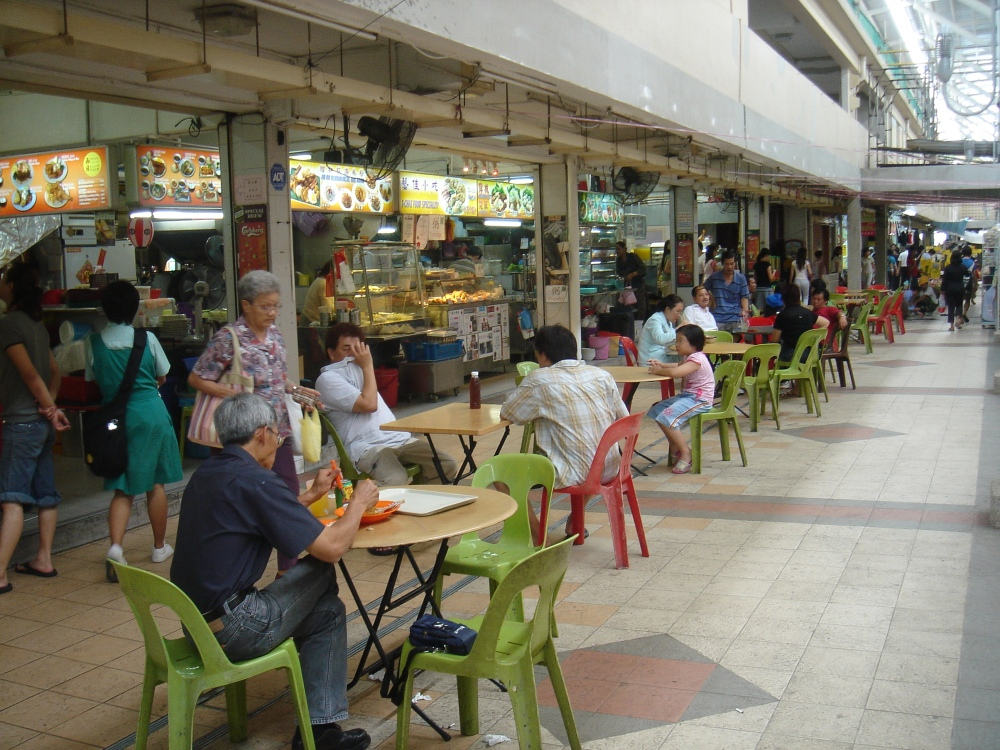 """A typical """"coffee-shop"""" in Singapore.  To Americans these local iconic institutions resemble outdoor food-courts.  Farrer reports that traditional martial arts masters would often socialize for hours with their students after class in the local coffee-shops.  In doing so they passed on the deep social knowledge that allowed the traditional martial arts to become a powerful form of social capital.  Source: Wikimedia."""