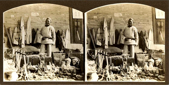 Stereoscope image of a junk dealer selling swords.  Probably late 19th century.