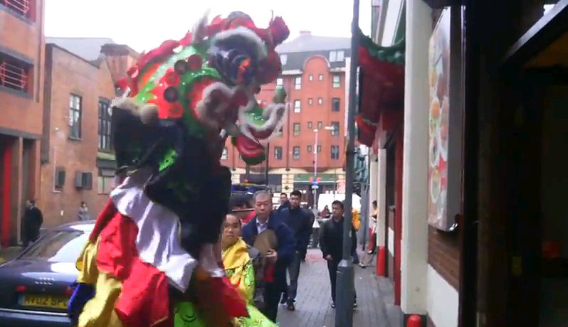 A towering Qilin prepares to ritually enter a Chinese restaurant, bringing good luck in its wake.  Birmingham's Chinatown, Lunar New Year, 2012.  Source: Chinatownology (see bellow for a link to the complete video).