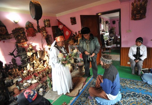 Kirati Shaman treats a patient in front of a huge altar collection.  Source: Tengri news, 2012.