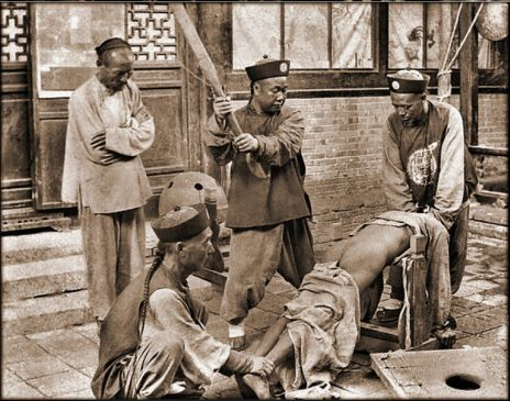 Qing era court officers beating a individual, either in an attempt to compel testimony or as punishment for some crime.  Original photographer unknown.  I am interesting in finding the original source of this image.