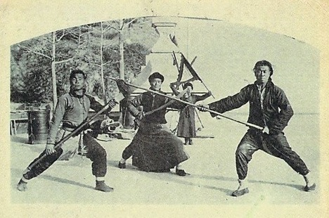 Detail of postcard showing traditional practitioners performing in a marketplace. Japanese postcard circa 1920.