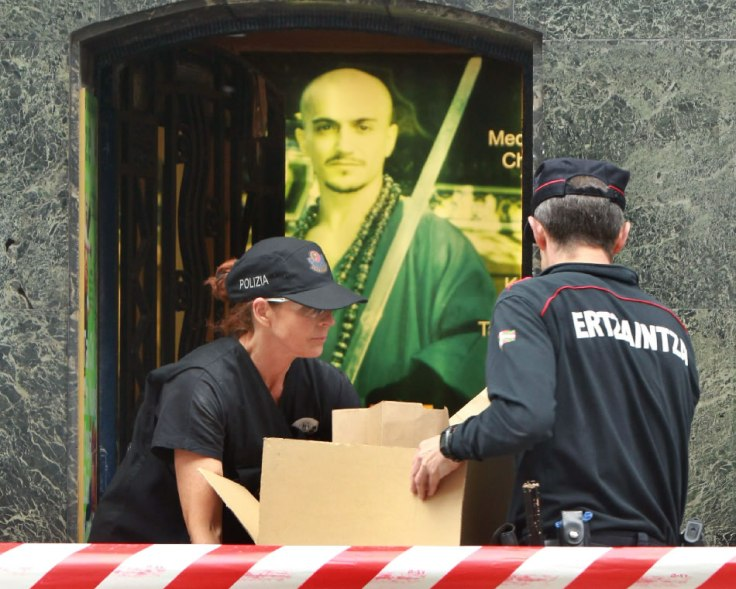 Police remove boxes of evidence from the school of xxxx in xxxx.  His image can be seen in the poster behind them.