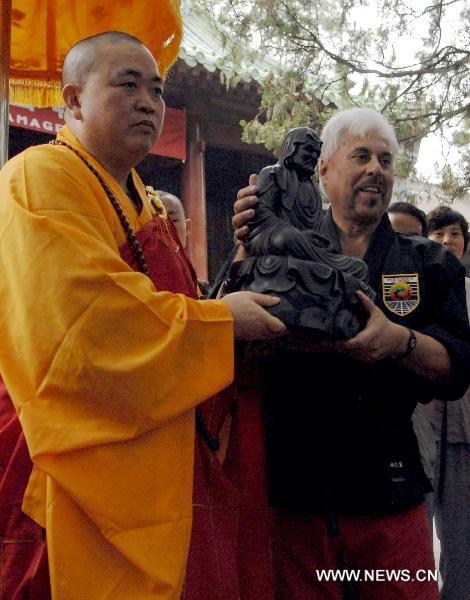 Shi Yongxin (L), current abbot of the Shaolin Temple, presents a sculpture of Bodhidharma to Professor Charles Mattera of United Studios of Self Defense (USSD) from the United States.