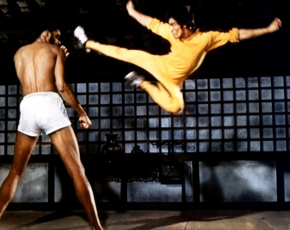 "Bruce Lee executes a spectacular flying kick while filming ""Game of Death."""