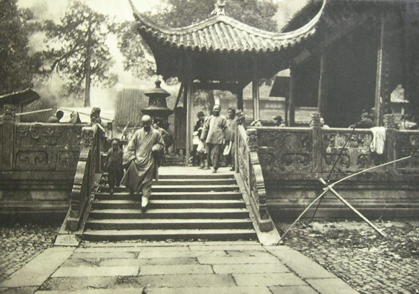 A Buddhist monk and novice leaving a the temple.  Probably Shanghai, circa 1900.