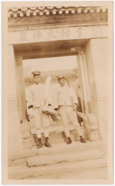 Dadaos held by two soldiers in front of a temple in Beijing.  Source: Author's personal collection.