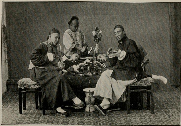 Gentlemen smoking both opium and tobacco pipes.  Source: Charles J. H. Halcombe. The Mystic Flower Land. 1896.