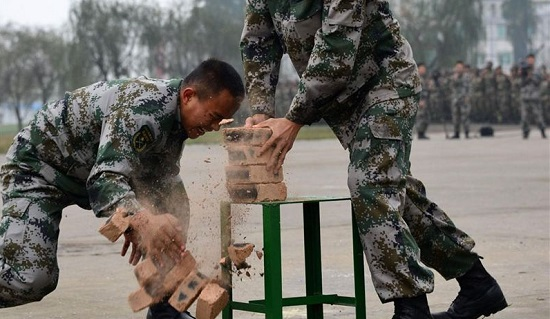A Chinese soldier using his head to break a number of bricks.  Source: www.chinawhisper.com