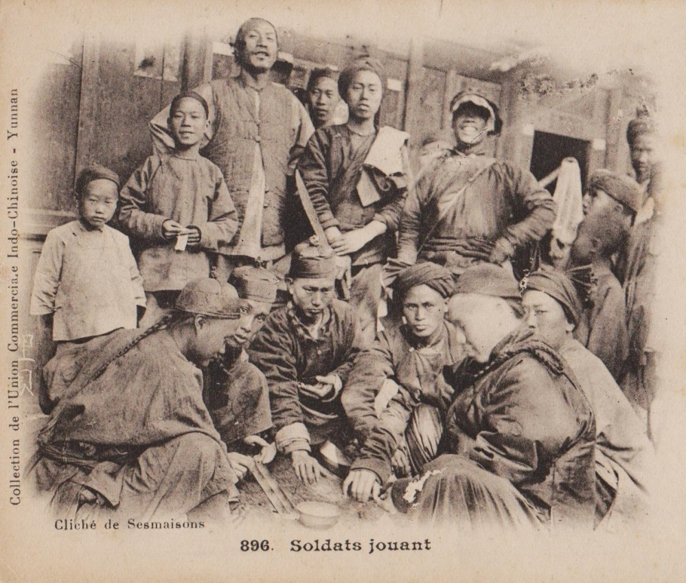 Image taken from a vintage french postcard showing soldiers gambling in Yunnan province.  Note that the standing soldier on the left is holding a hudiedao in a reverse grip.  Source: Author's personal collection.