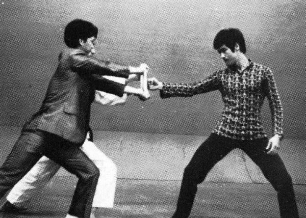 Bruce Lee demonstrates the one inch punch.  Simultaneously exhibits a great 1970s fashion sense.