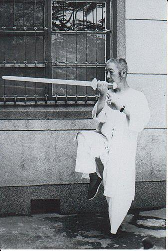 Zheng Manqing, the teacher of William Chen, with sword, possibly on the campus of Columbia University in New York City.