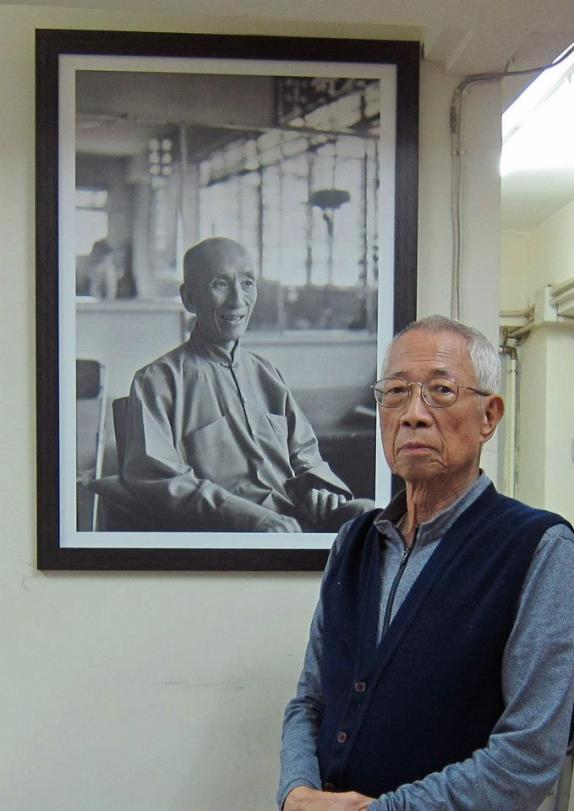 Wing Chun Master Chu Shong Tin standing next to the portrait of his teacher, Ip Man. Source: http://pangea.com.hk
