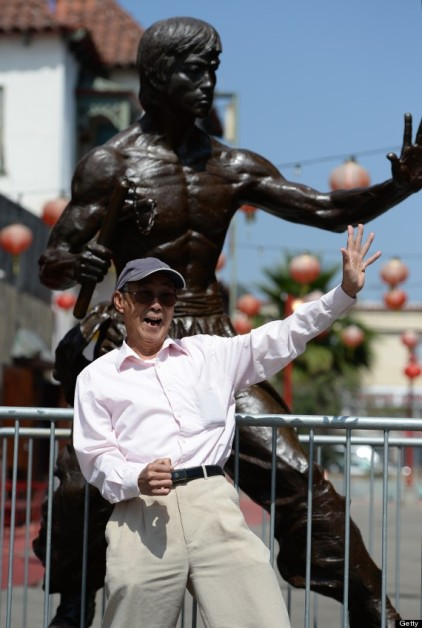 Another individual sharing a moment with the image of Bruce Lee, LA Chinatown.  Source: Huffington Post.