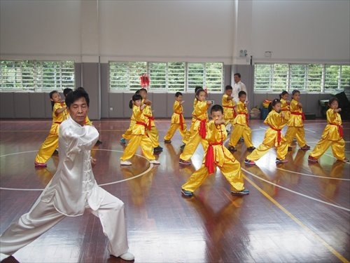 Chen Daoqing, a third-generation practitioner of Mian Quan, leads students practicing moves at Shanghai Kunming Primary School.  Source: Global Times