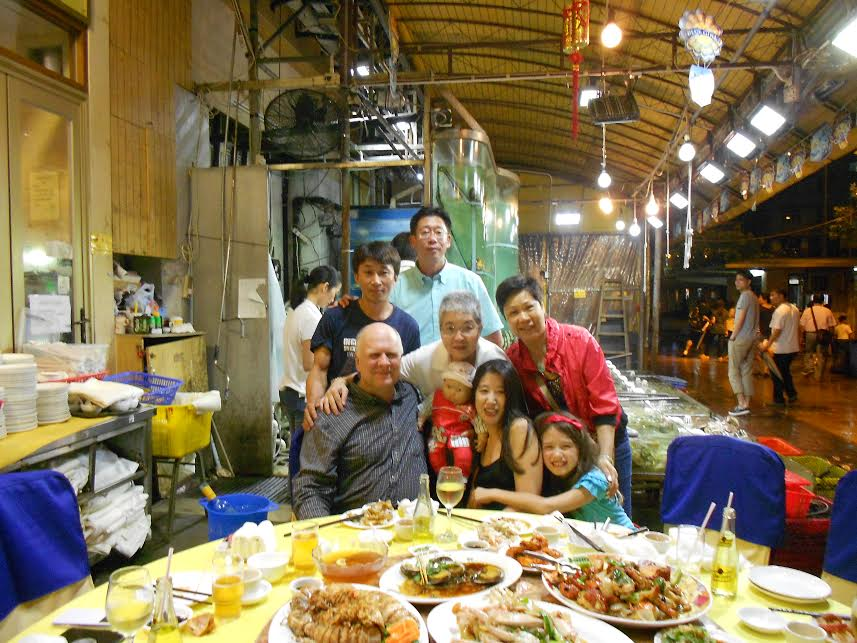 Martial sister (with arm on my shoulder) and martial brother (tallest person standing in the rear of the photo), consuming seafood with their and my family members and friends.  Both have followed the master since childhood, and my martial sister is a member of the master's patriline.   My martial brother in the photo serves as the master's teaching assistant. He is a policeman, a common occupation for someone from Hong Kong's New Territories with little education.  Although he did not receive much education, his son is a graduate of an Ivy League school in the U.S. and currently works for an international banking firm in Hong Kong.  His son is also a capable martial artist, and considered a follower of the master.   Source: Amos' Personal Collection.