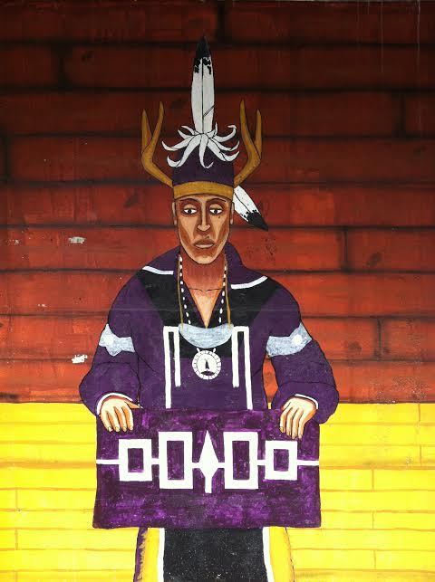 A detail of a larger mural painted on a parking garage next to the Ithaca Commons (in Ithaca NY) showing an Iroquois chief holding a wampum belt that represents the nations of the confederacy.  Photo by Benjamin Judkins.