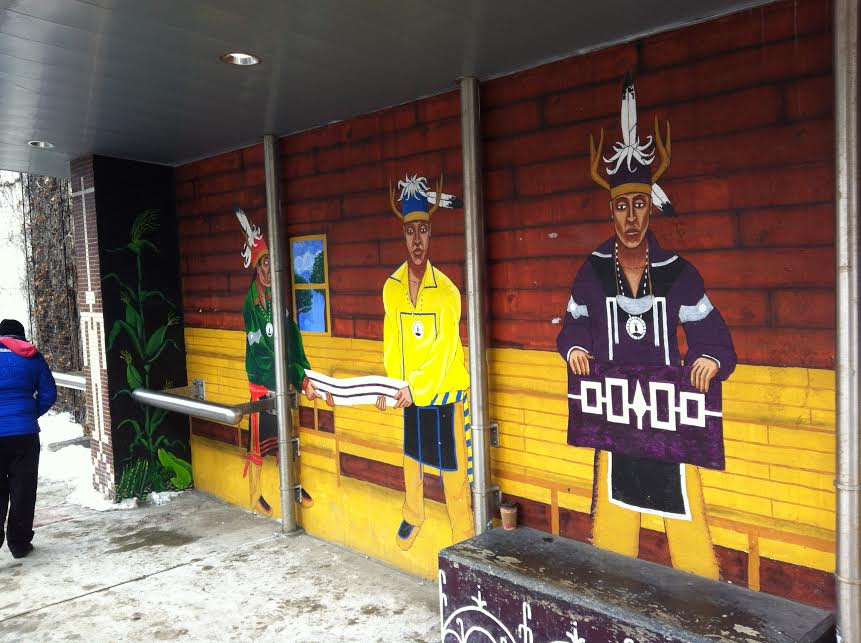 A longer view of the same mural.  Note that the figure are portrayed as standing within a modern longhouse.  Photo by Benjamin Judkins.