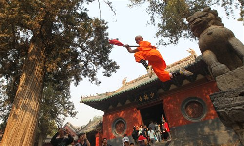 A student from a martial art school performs in front of the Shaolin Temple in Dengfeng, Henan Province on October 13, 2013. Photo: IC.  Source: Global Times