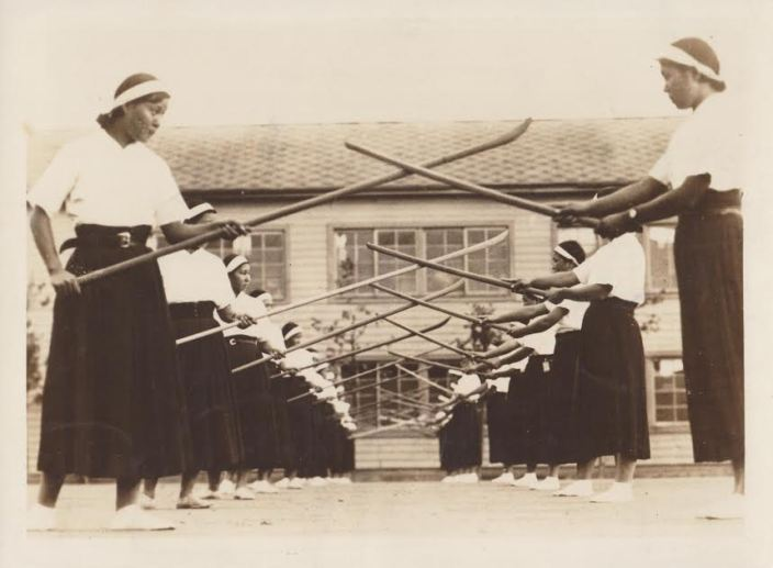 "A press photo issued by the Japan Press Illustrated Service.  The caption on the back reads ""Instruction of Halbert and Sword.---The halbert has been instructed from old as a peculiar Japanese military art of women that trains them spiritually at the same time according to then spirit of chivalry.  Photo shows girls of the Fifth girls high school of Tokyo practicing the art. (Copyrighted 231). JPI Photos.""  Source: Author's personal collection."
