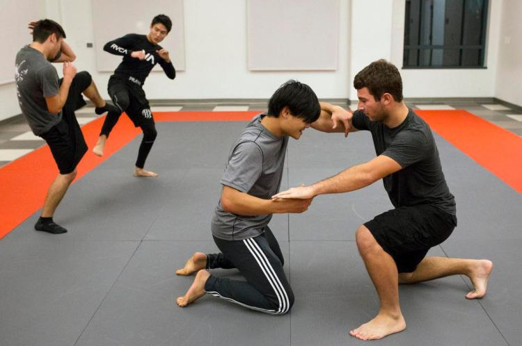 Zach Woznicki, right, and Karn Charoenkul, center, lock arms while Justin Sanchez, left, and Ian Cabeira battle in the background during an open practice held by Chapman's Martial Arts Club on Thursday. ????///ADDITIONAL INFORMATION: 12/3/15 - FOSTER SNELL, ORANGE COUNTY REGISTER - ch.martialarts.1215 Ð This request is for our feature on the Chapman Martial Arts Club. The club will have open practice at 7 p.m. Thursday, Dec. 3. We'll want shots of the students practicing various styles of martial arts
