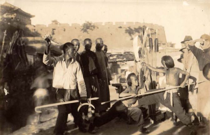 A photograph (probably 1930s) showing a marketplace martial arts demonstration.  Note the Shuang Gau led by the man on the left.  Source: The personal collection of Benjamin Judkins