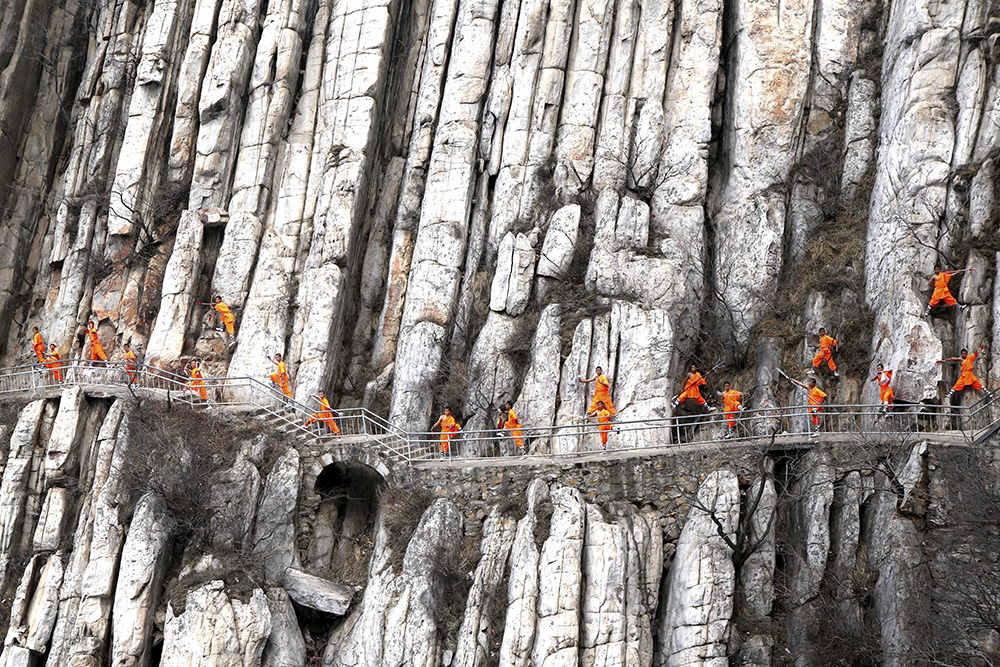Students from a martial arts school practice Shaolin Kung Fu on cliffs in Dengfeng, Henan Province, China, March 17, 2016. REUTERS/Stringer