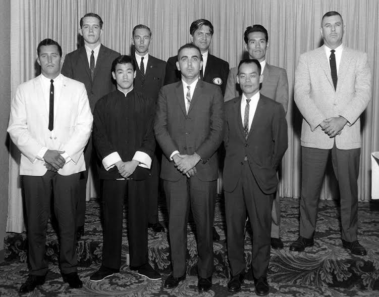"""Long Beach: """"He just started trashing people."""" A young Bruce Lee, bottom row second from left, standing with other presenters at Ed Parker's inaugural Long Beach International Karate Tournament in the summer of 1964. J. Pat Burleson, Bruce Lee, Anthony Mirakian, Jhoon Rhee. Back Row, Left to Right: Allen Steen, George Mattson, Ed Parker, Tsutomu Ohshima, Robert Trias. Source: Photo courtesy of Darlene Parker."""