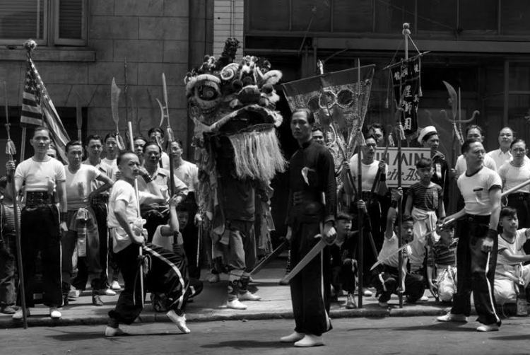 TY Wong standing with butterfly swords, center, during a San Francisco street parade during the 1940s. Source: Photo courtesy of Gilman Wong.