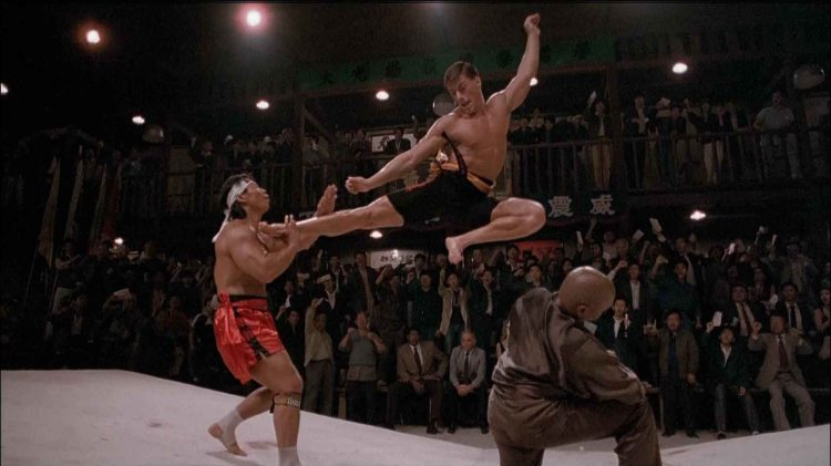 Jean Claude Van Damme demonstrates a flying sidekick in Bloodsport. While the quality of this film won't seem any better after reading Now With Kung Fu Grip!, why it was made (and achieved such popularity) will make a lot more sense.