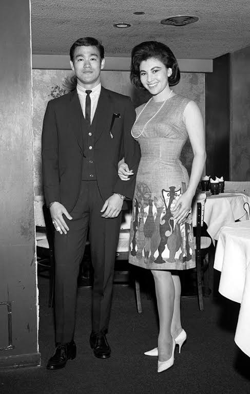 """Hong Kong starlet Diana Chang Chung-wen (""""the Mandarin Marilyn Monroe"""") photographed with Bruce Lee in late summer of 1964 during a promotional tour of the U.S. west coast in support of her latest film. This brought them to the Sun Sing Theater, in the heart of San Francisco's Chinatown where Bruce's martial arts demonstration (and critical lecture) nearly resulted in an on-stage brawl in front of a riotous audience. Weeks later, Bruce would face down Wong Jack Man in a legendary behind-closed-doors high noon showdown, based largely on comments he made from the stage of the Sun Sing Theater, as well as long list of incidents with other members Chinatown's martial arts community. (Photo courtesy of UC Berkeley)"""