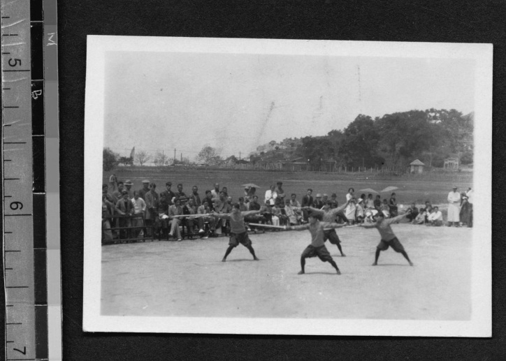 "The archival note with this photo reads as follows: ""F. C. U. student activities ""F. C. U. Girl athletes Chinese boxing"" Four students in blouses and bloomers, holding sticks in their right hands, perform a move on a dirt field surrounded by walls. A crowd of spectators watches. Hills visible in background.""  Source: http://findit.library.yale.edu"