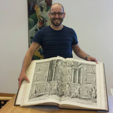 Dr. Sixt Wetzler showing off a fight book from the collection of the German Blade Museum.